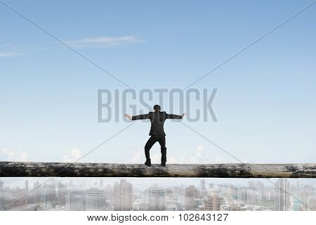 Rear View Businessman Balancing On Tree Trunk High In Sky
