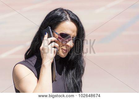 Caucasian Brunette In Sunglass Talking By Mobile