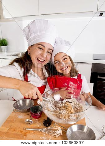 Happy Mother Baking With Little Daughter In Apron And Cook Hat With Flour Dough At Kitchen