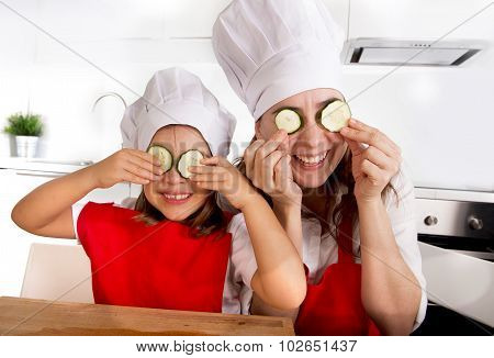 Mother And Little Daughter In Cook Hat And Apron Playing With Cucumber Slices On Eyes In Kitchen