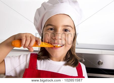 Little Girl At Home Kitchen In Red Apron And Cook Hat Holding Carrot And Biting Happy
