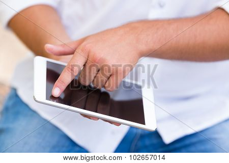 close up of young man using internet on digital tablet
