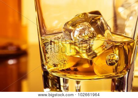 Detail Of Glass Of Whiskey With Ices Near Bottle On Table With Reflection, Warm Atmosphere