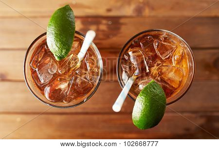 two glasses of iced sweet tea with lime and retro paper straws shot overhead on wooden table