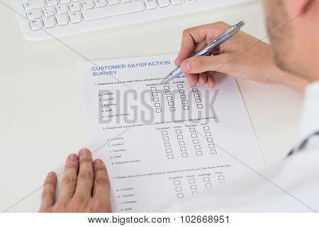 Person Hands Filling Survey Form