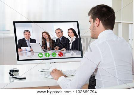 Businessman Videoconferencing On Desktop Computer