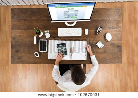 Businessman Calculating Tax With Computer At Desk
