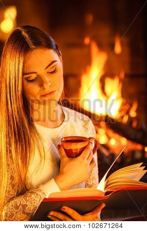 Woman Drinking Coffee Reading Book At Fireplace.