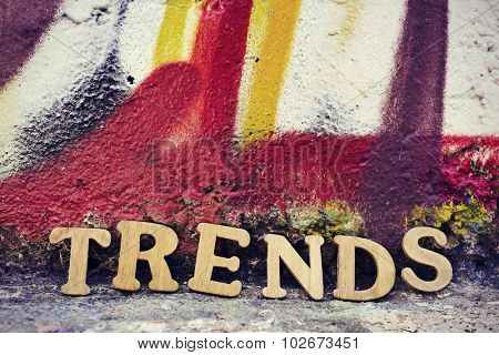 wooden letters forming the word trends on a wall painted in different colors
