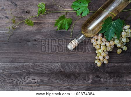 Bottle Of White Wine And Fresh Grape On Wooden Background