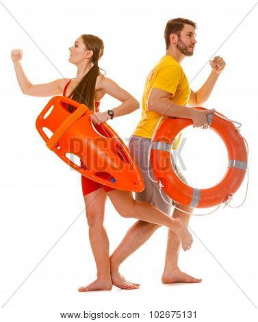 Lifeguards Running With Rescue Ring Buoy On Duty.