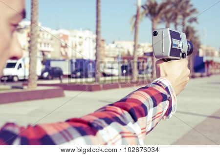 closeup of a young man wearing a red plaid shirt points a retro film camera like it was a gun, in a urban scenery
