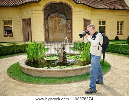 Professional Photographer With Backpack And Dslr In The Baroque Garden