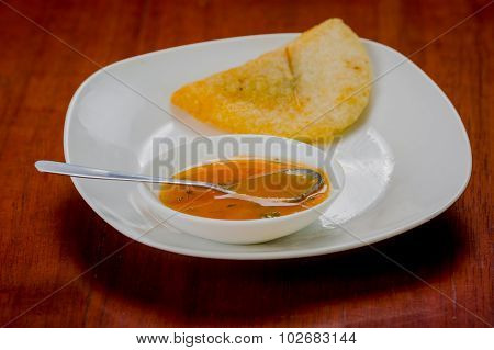Delicious empanada placed on white plate with small salsa bowl