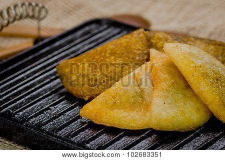 Closeup five empanadas lying in fan formation on black metal grill tablet