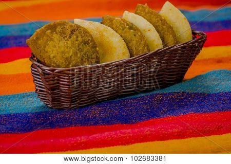 Basket with six empanadas neatly placed inside sitting on latin colorful table cloth
