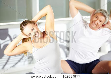 Woman stretching in group in gym during back training