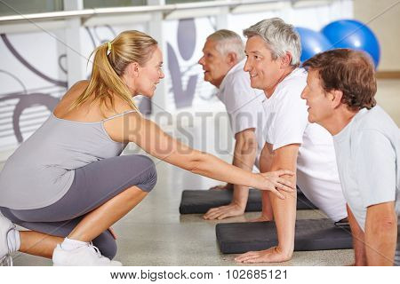 Fitness instructor helping senior people in gym during back training class
