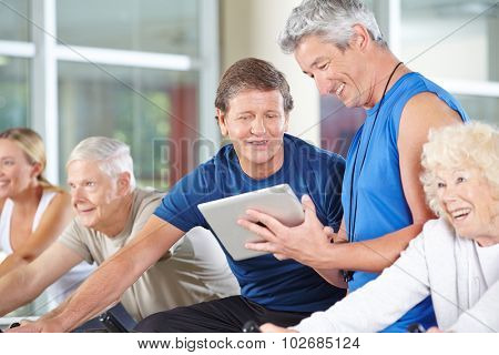 Fitness trainer with tablet computer in gym talking to senior people