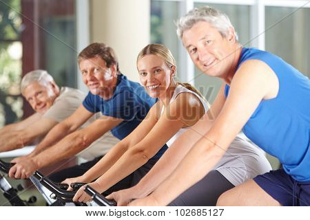 Group of happy seniors on spinning bikes in gym