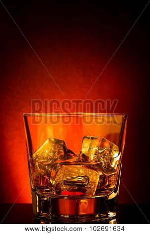 Glass Of Whiskey On Black Table With Reflection, Red Tint Atmosphere
