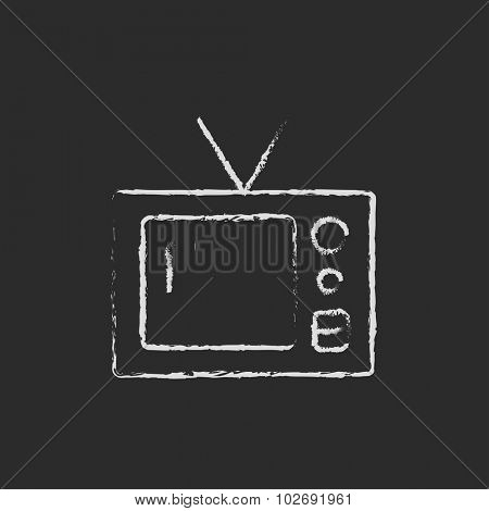 Retro television hand drawn in chalk on a blackboard vector white icon isolated on a black background.
