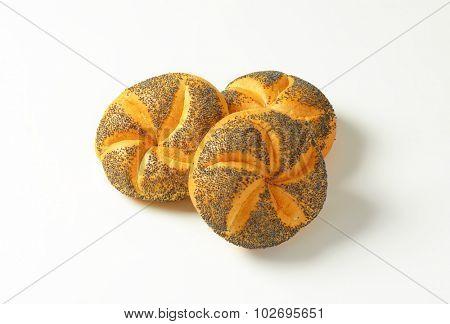 three fresh poppy seed buns on white background