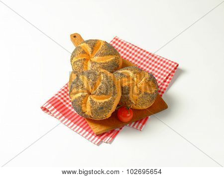 fresh poppy seed buns on wooden cutting board and checkered dishtowel