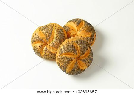 three fresh poppy seed buns on white background