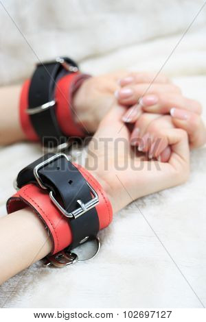 female hands in leather handcuffs. on the background sheet. sex toys.
