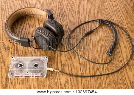 Brown Headphones With Long Rubber Cable Connected To The Tape