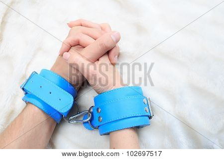 Male and female hands in handcuffs. sexy couple in bed. sex Toys