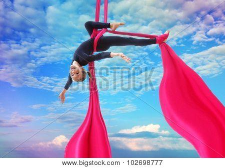 Child Hangs Upside Down On Aerial Silks In Sky
