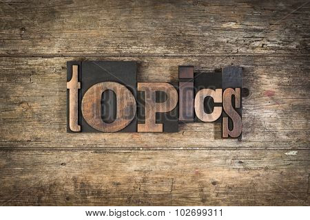 Topics, set with vintage letterpress printing blocks on wooden background
