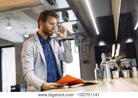 Businessman Drinking Water And Reading Paper