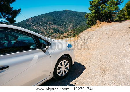 White color small hatchback car on Spainish nature mountains lan