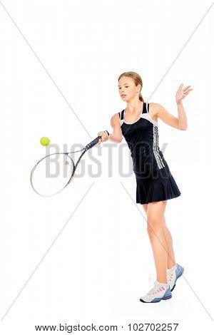 Full length portrait of a girl tennis player in motion. Studio shot. Isolated over white.