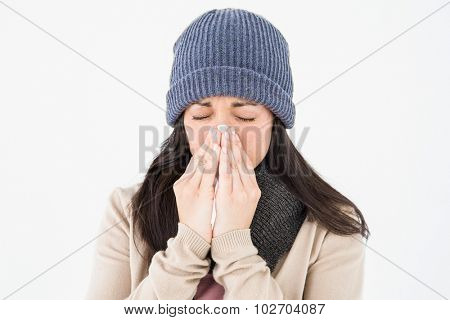 Sick brunette blowing her nose on white background