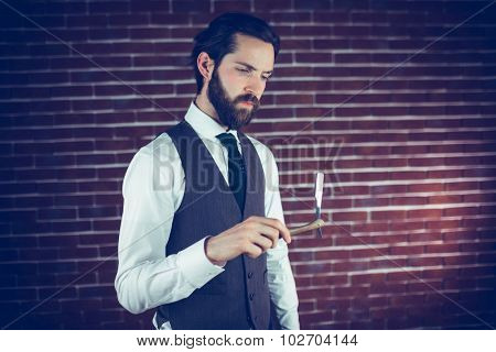 Serious man holding razor against brick wall