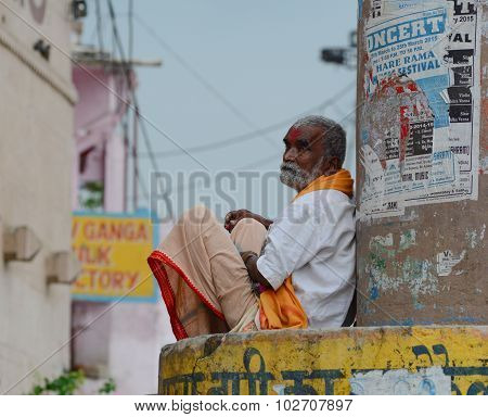 Indian Man Sitting At The Ghat In Varanasi