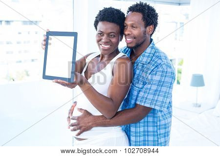 Happy couple looking towards digital table while embracing