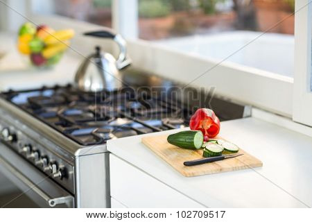 Vegetables on chopping board on counter top in kitchen