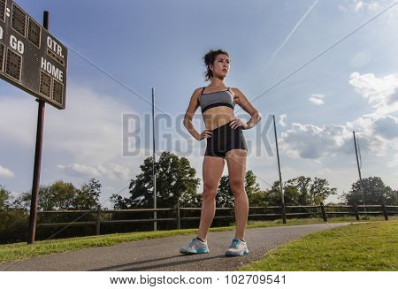 An athletic female exercising on a track outdoors