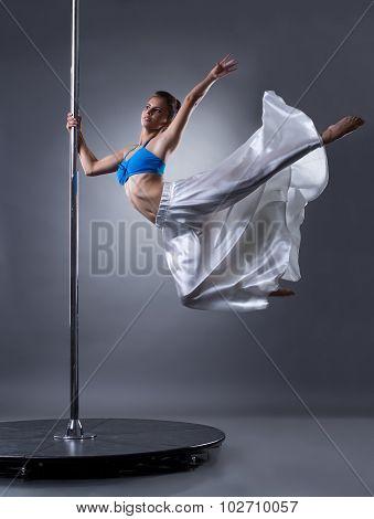 Pretty female dancer turning around pylon