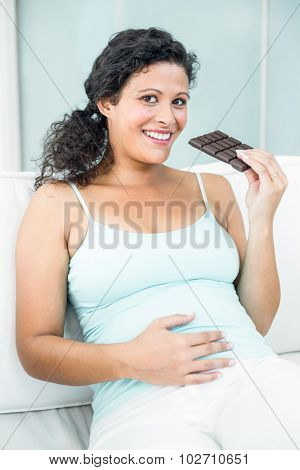 Portrait of happy pregnant woman with chocolate bar sitting on sofa