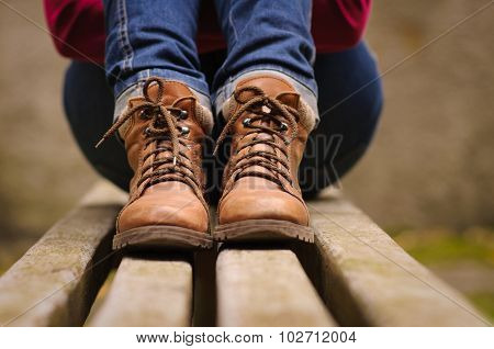 girl sitting on a bench in the boots