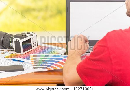 Man working on laptop with camera and palette, colormap spread out next to it