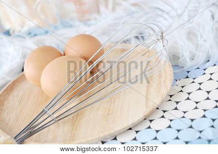Whisk And Eggs On Wooden Plate