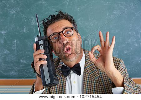 Nerd silly private investigator with retro walkie talkie on teacher blackboard