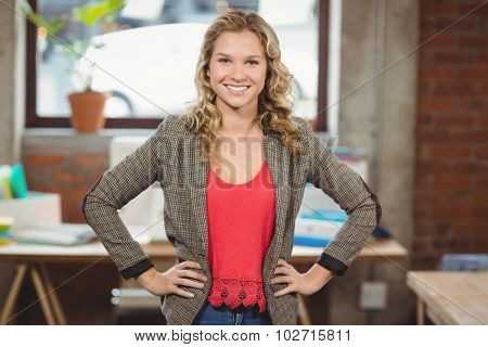 Portrait of confident businesswoman with hands on hip standing in bright office